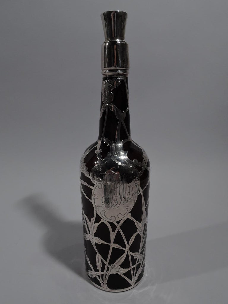 Art Nouveau amber glass whiskey bottle decanter with silver overlay, circa 1900. Traditional cylindrical form with sloping shoulder and upward tapering neck. Open and interlaced silver overlay with thistle ornament and asymmetrical cartouche with