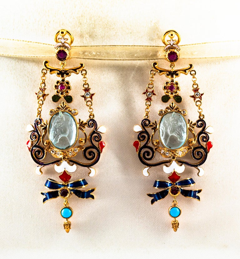 These Earrings are made of 9K Yellow Gold. These Earrings have  0.30 Carats of White Modern Round Cut Diamonds. These Earrings have 0.60 Carats of Rubies. These Earrings have two Carved Blue Topaz representing two horses. These Earrings have