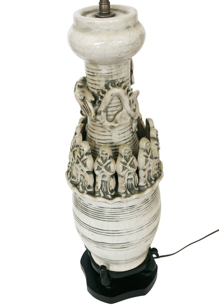 The work is a white art pottery lamp of a cylindrical shape with wood base. The lamp is decorated with 12 monks that surround a dragon. The lamp also has decorative, horizontal patterns and crackle finish. Carved out of the wood base that holds the