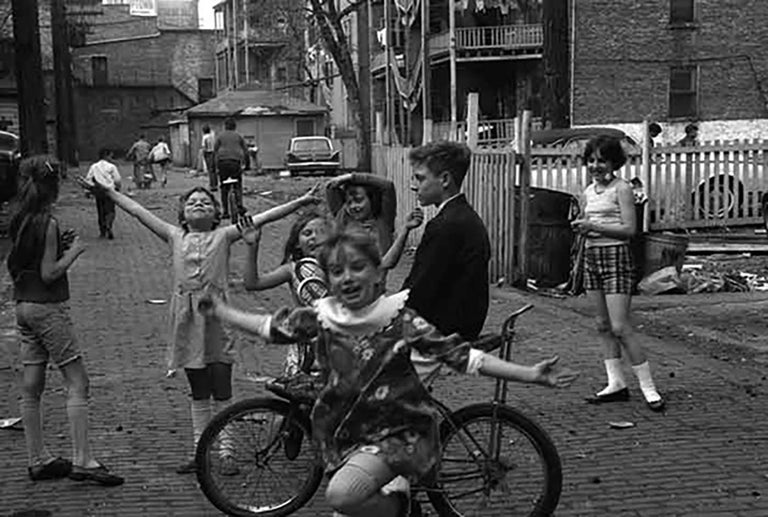 """Art Shay's love of Street Photography is evident is this 1958 photograph entitled """"Back Alley Joy"""".  Happiness exudes from the children playing in this alley in an unidentified Chicago neighborhood.  The photograph is signed in the bottom right"""