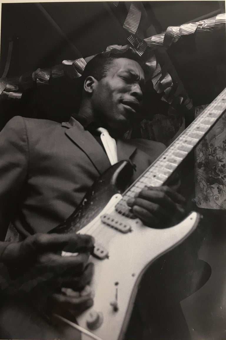 Considered one of the greatest guitarists of all time, this black and white photograph of Buddy Guy was taken by Art Shay in 1966.  In 2016, Buddy Guy chose this photo for his 80th birthday celebration poster.  It is signed on the front of the