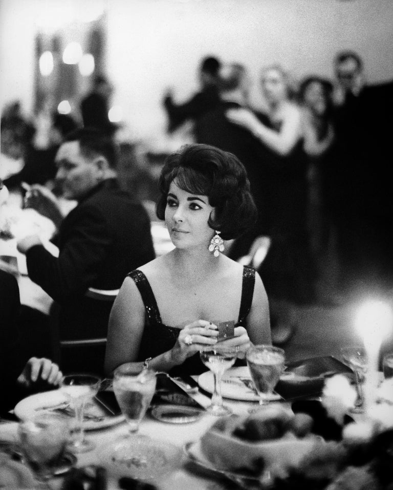Art Shay captures Elizabeth Taylor in all her glory in this iconic photo taken in 1960 at Chicago's famed Pump Room Restaurant.  The photo is a silver gelatin print, signed by the artist on the back.  The frame is a simple black metal with a heavy