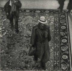 10 P.M. Dallas (Man in hat walks across an Oriental carpet in Dallas hotel)