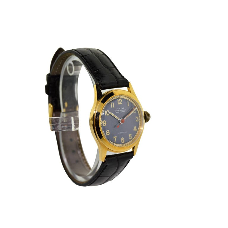 FACTORY / HOUSE: Arta Watch Company STYLE / REFERENCE: Art Deco  METAL / MATERIAL: 14kt. Yellow Gold CIRCA: 1950's DIMENSIONS: 35mm X 29mm MOVEMENT / CALIBER: Manual Winding / 17 Jewels  DIAL / HANDS: Original Blue Luminous Arabic Numerals /