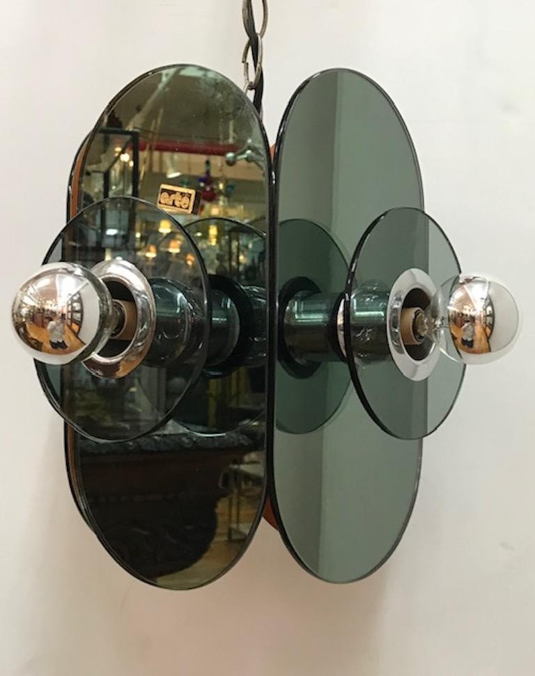 A 1970s optical mirror pendant light by Italian home design company Arte Linea. Four smoke mirror side panels and one bottom panel make up the body of the pendant light. Extended from each side mirror is a chrome socket cover with a clear smoke