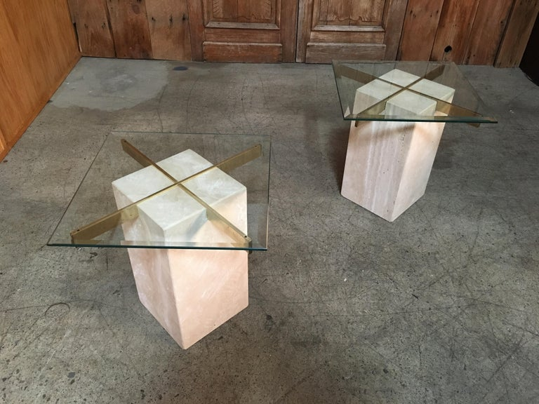 Two hollow cubes of travertine marble with brass plated X supports for the beveled glass