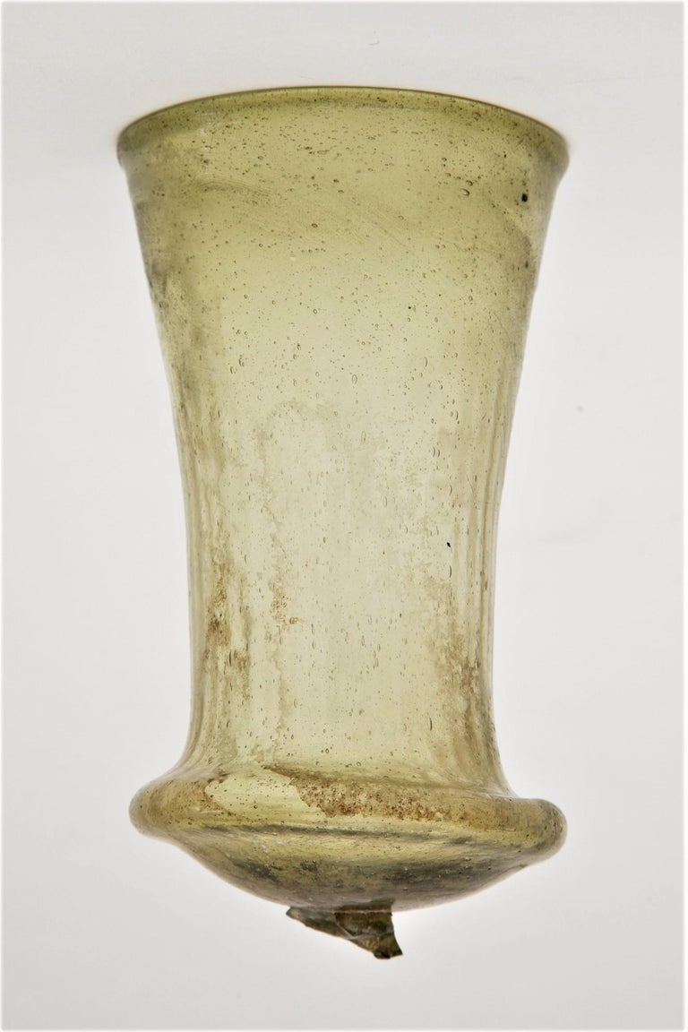 Late Roman Merovingian Glass Bell Beaker secular art from the Country: Germany / Krefeld. Culture: Merovingian.Date: 6th century AD.Material: Pale yellow, pattern molded, transparent glass. Decorated with thin vertical ribs. Conical in form with