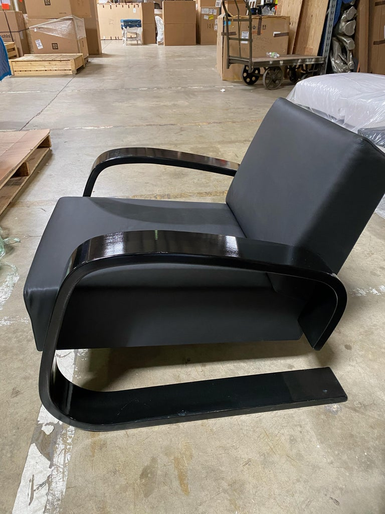 """As voluminous as it is comfortable, Armchair 400 was created by Alvar Aalto in 1936 for an exhibition at the Milan Triennale, where it was promptly awarded a prize. The chair owes its nickname """"Tank"""" to its distinctive wide and sturdy armrests made"""