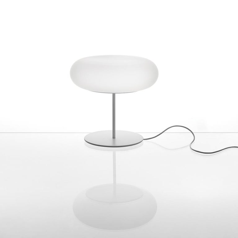 Magnificently simple and powerful, Naota Fukasawa's Itka subtly but uniformly spreads light.  Made of opaline frosted glass on a white lacquered metal base, the table lamp is LED and CFL and dimmable.  Materials: Base in metal painted