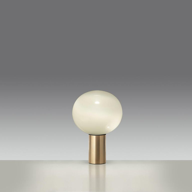 Now available in stunning gold, Laguna table is a spherical table lamp with raised base provides a softly diffused light on the tabletop and casts a warm light in its surrounding environment.  This modern and elegant table features handblown glass
