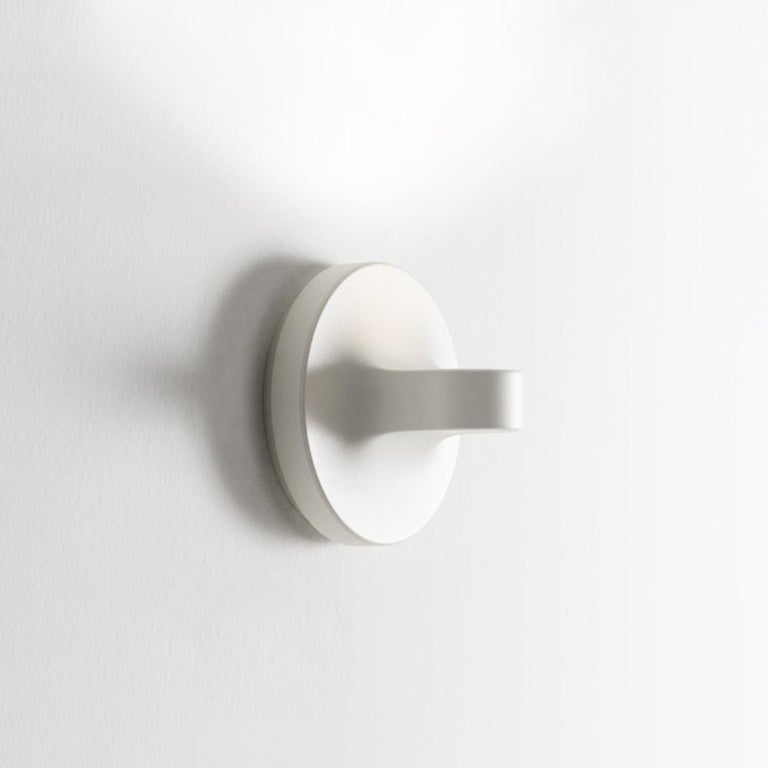 Tigia is a wall lamp with an elementary shape and a small size to meet the ADA standards, which provide for minimum protrusion. Starting from the size constraints related to these functional traits, the optical unit was designed in view of ensuring