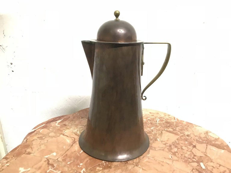 Arthur Dixon, designed for Birmingham guild of handicrafts. An Arts & Crafts copper and brass jug and lid with rat tail handle. Stamped