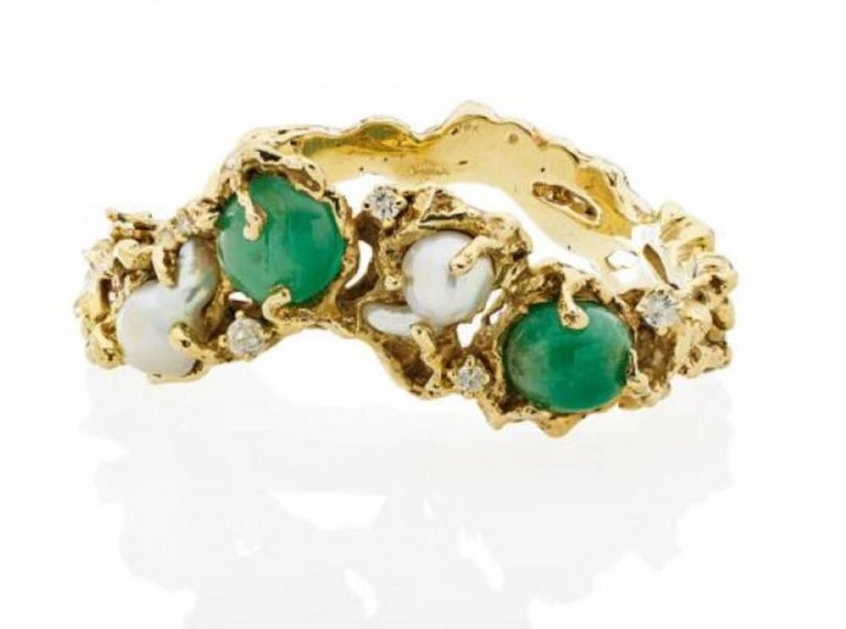 A wonderfully organic 1970's 18k yellow gold, cabochon emerald, south sea baroque pearl, and diamond hinged bangle bracelet by the famed American jeweler, Arthur King (1921 - 1991). Fits up to a 7