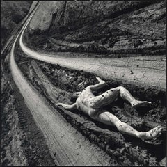 Road Kill (a nude male lies in the deep ruts of a muddy curved trail)