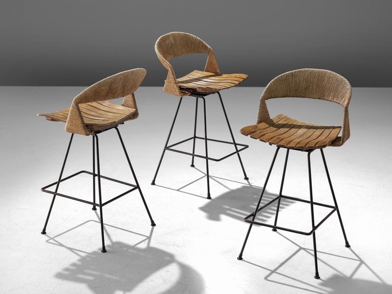 Arthur Umanoff for Raymore, set three bar stools, iron, cane and plywood, United States, 1950s  A set of three barstools by Arthur Umanoff for Raymor. The stools consist of an iron base with a squared frame for the sitter to rest their feet. The
