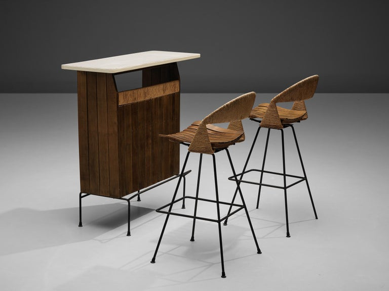 Arthur Umanoff for Raymor, dry bar, pair of bar stools, wood, iron, cane, United States, 1960s  The dry bar by Arthur Umanoff rests on a slim iron base that has a footrest in front. Vertical wooden slats end in a line highlighted in cane that flanks