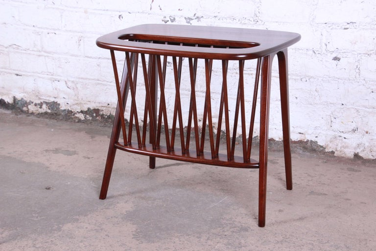 Offering a very sleek solid walnut magazine rack or side table by Arthur Umanoff. The rack has been newly refinished and offers a nice sized slot for magazines or other items with a small area to act as a table top. This piece has sleep Mid-Century