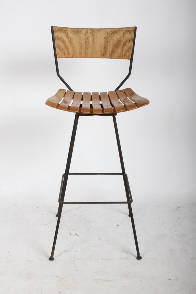 Single Arthur Umanoff swivel bar stool, wood slat seat, iron frame with Danish rush cord wrapped back. If you need another stool to complete your set, here is one that is left unrestored, so you can match. Frame retains original glides, some rust to