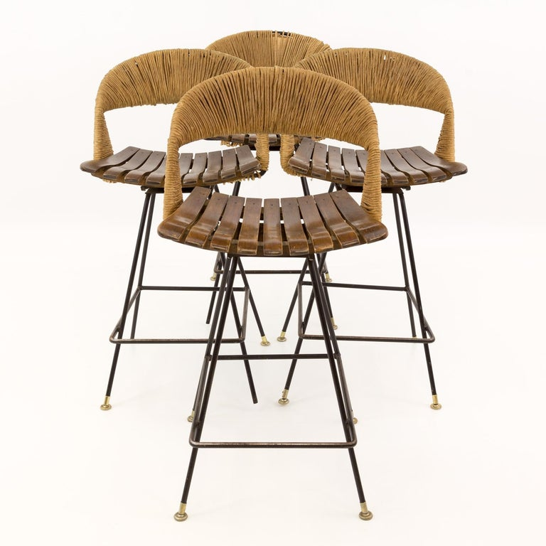 Arthur Umanoff Mid Century Tiki iron bar stools - Set of 4 Each stool is 18.5 wide x 20 deep x 35 high with a seat height of 25 inches  All pieces of furniture can be had in what we call restored vintage condition. This means the piece is restored