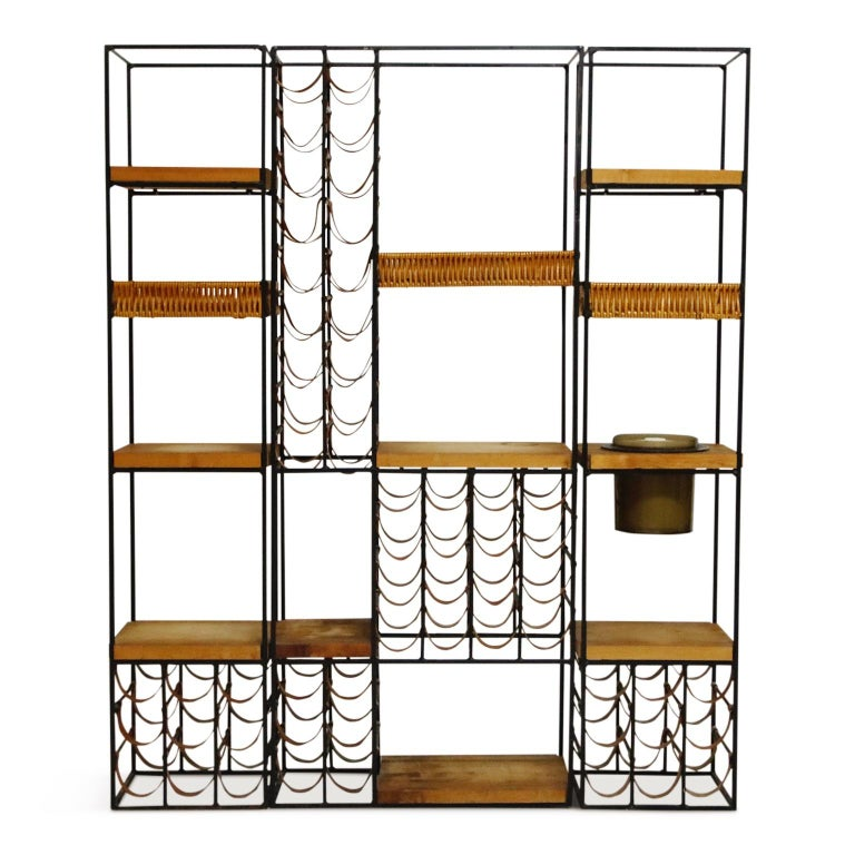 The ultimate entertaining piece, this Arthur Umanoff three (3) section wine rack system and room divider which also incorporates an artful array of fifty-eight (58) leather wine bottle holders, three (3) wicker baskets, eight (8) butcher block