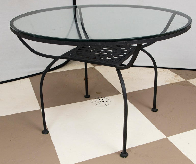 Arthur Umanoff wrought iron sun table with four sun back armchairs with ball finials. Table is 42 inches in diameter and 29.5 inches high. Glass is new. Seats need reupholstering.