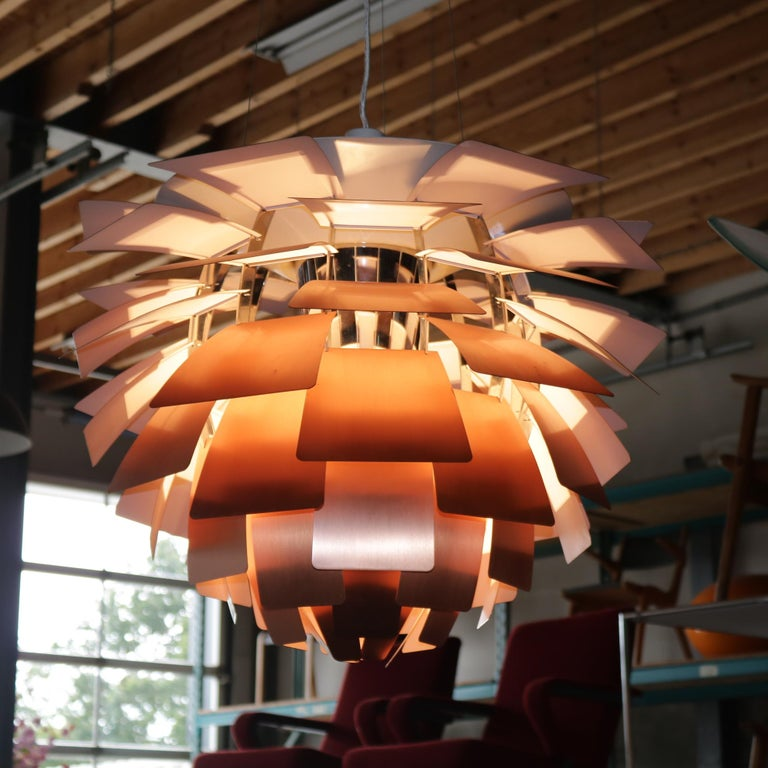 Stunning lamp, model Artichoke designed, by Poul Henningsen in 1958 and manufactured by Louis Poulsen (Denmark) in the early 1960s.  The lamp has a chrome-plated metal inner diffuser and stainless steel cables. The eye-catching feature is, of