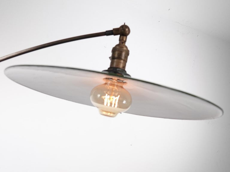 The lines on this lamp are beautiful. The base is delicate cast iron with 4 curved legs and small wooden wheels. The base also has a small rack to hold books... and it does make perfect reading light. The articulated arm that holds the lamp also has
