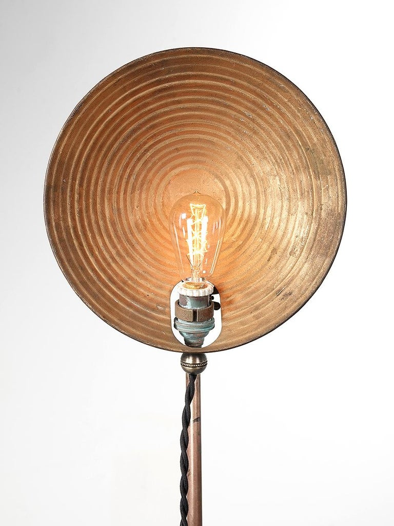 This is a very simple, light and elegant brass and tin floor lamp. Its 1920s Industrial but looks very modern and high style. The tin shade has a stepped ring pattern showing a nice original patina. The stand and base are solid brass.