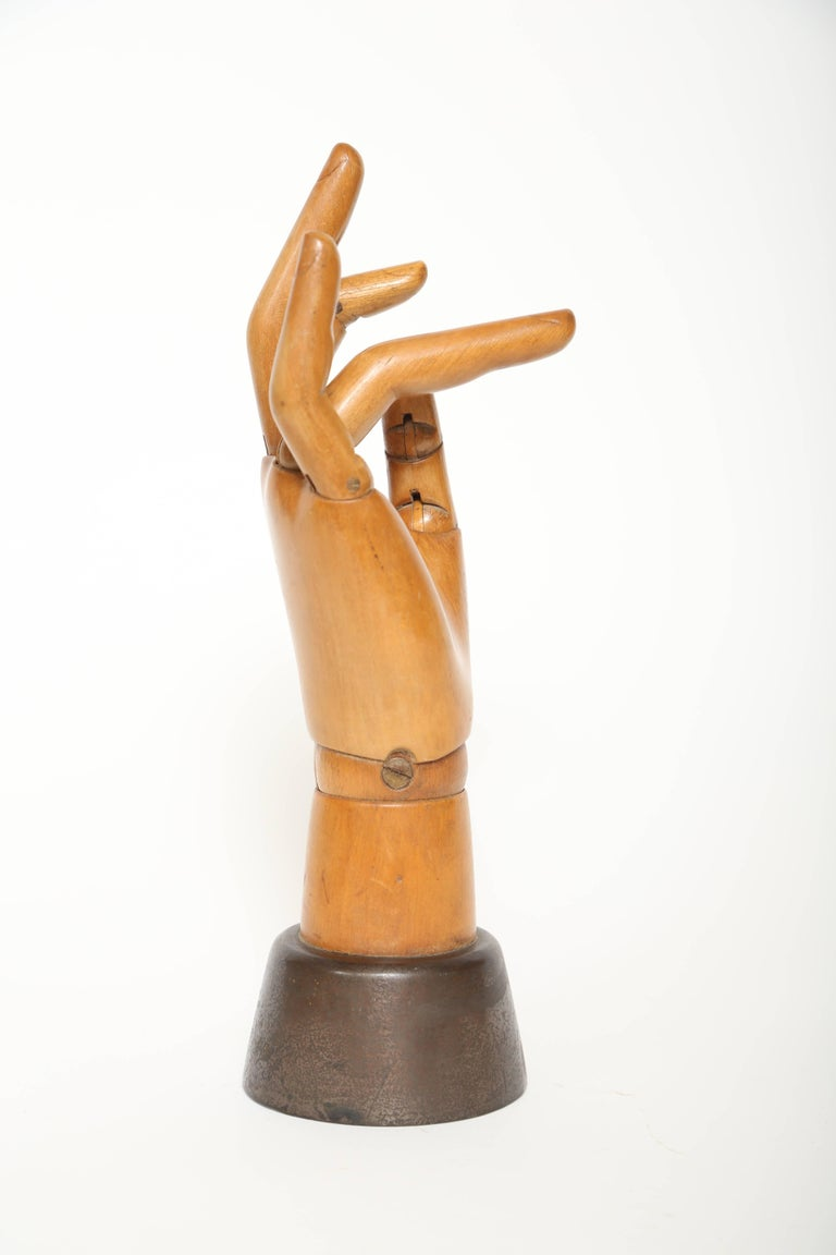 Life size articulated wooden hand mannequin with a weighted iron base. Used by artists and sometimes by shops to display gloves, jewelry and so on.  This piece is great quality with nicely carved fingers and finger nails displaying good honey color