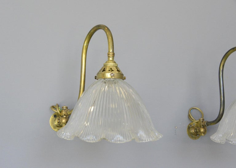 Articulated wall sconces by Holophane, circa 1910  - Price is per light (3 available) - Articulated curved brass arms - Fluted prismatic shades - Takes B22 fitting bulbs - Wires directly into a wall feed - English, 1910 - Measures: 24cm wide
