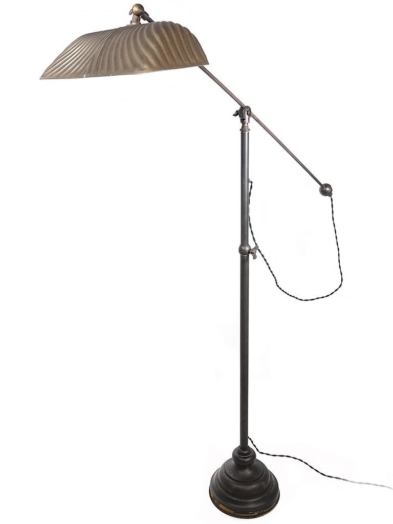This is a beautiful all brass articulated floor lamp. The shade is a rare 14 inch wide X-Ray mirrored mercury glass. The mirror is foxed and original the outside paint has been refinished to a dark gold.