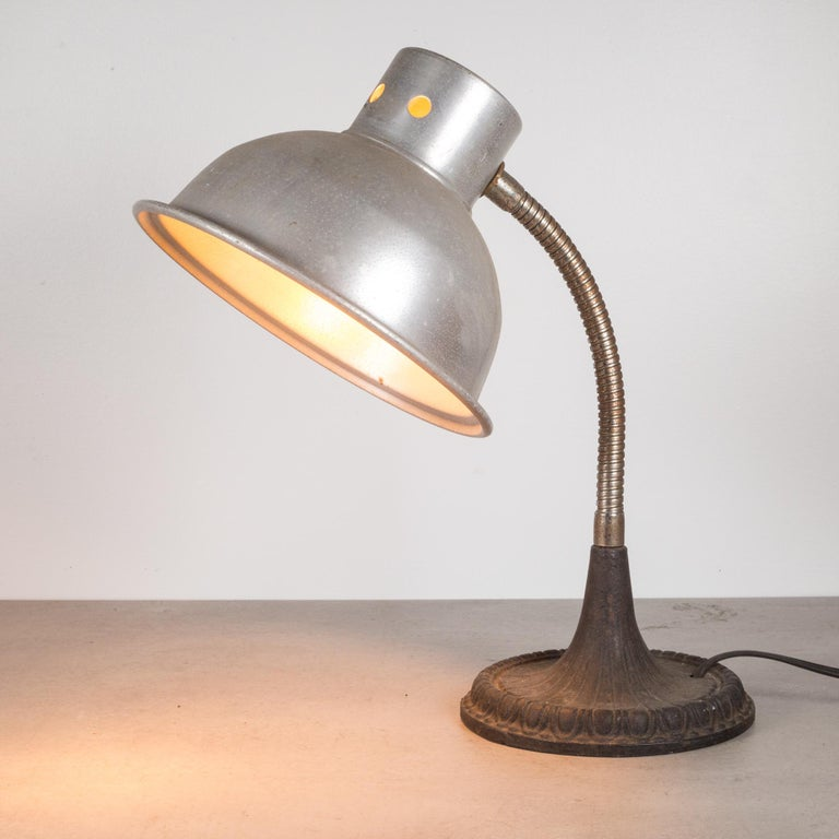 About  An antique gooseneck task lamp with aluminum shade, articulating arm and cast iron base. The light bends and adjusts on the arm.  Price per piece.  Creator: M. Brandt and Sons, Bronx, New York. Date of manufacture: