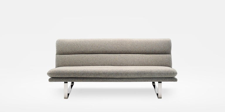 A sofa by Kho Liang Ie. Restrained simplicity. Frame of pressed beech upholstered with moulded foam on a metal base. With integrated seat and back cushion.
