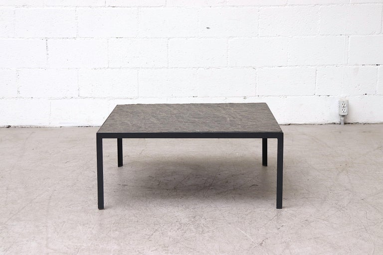 Incredible square coffee table with inset textured stone top and grey enameled metal frame. In original condition with minimal visible wear to top and frame.