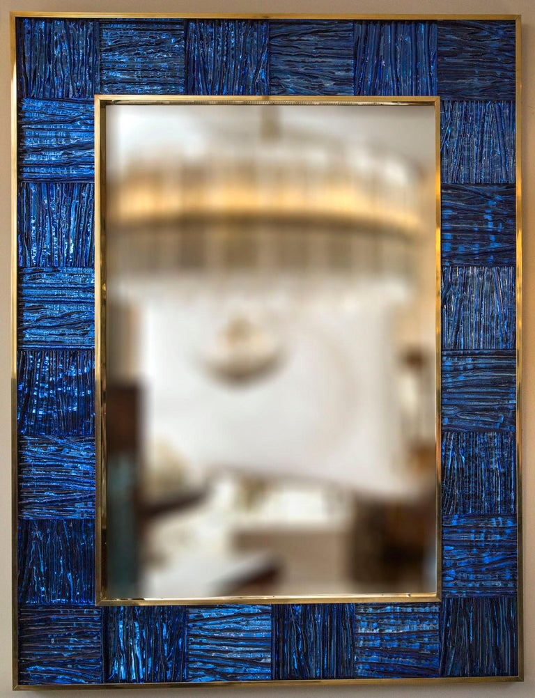 Striking un-lacquered brass framed mirror inset with thickly blown wavy textured glass panels in a Klein blue tone, artisan metal and glass work. Weight 70-75 lbs 1 available or customize-able in size and color Date: contemporary Origin: Venice,