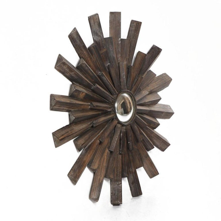 Sunburst mirror, artisan constructed from old barn wood then waxed, creating a cerused effect. The center is a small convex mirror with antiqued silvering. Each piece is hand sawn in an elongated triangular shape, not flat like some mass-produced