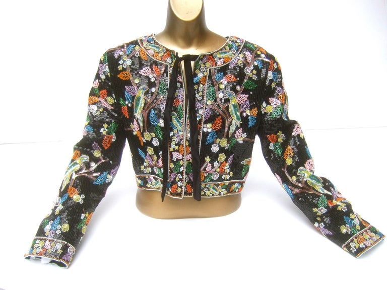 Exquisite glass beaded artisan birds of paradise floral sequined bolero style jacket c 1980s The incredible glass beaded bolero style jacket is designed with an intricate, elaborate  hand beaded scene of a series of birds perched on tree branches.