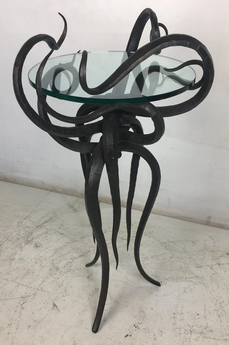 An incredible Artisan wrought iron tour de force is this sculptural side table or plant stand. The twelve tendrils cradle a glass top in its center as it stands on its flowing legs. The workmanship and design on this table is top quality in every