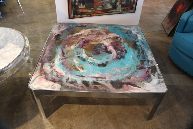Artist, Marco Antonio, used the glass top of this table to paint a beautiful abstract. it is Epoxy paint decorated glass top on a Vintage 1980s chromed steel base. The abstract art top is colorful and vibrant. There are some minor marks on the base