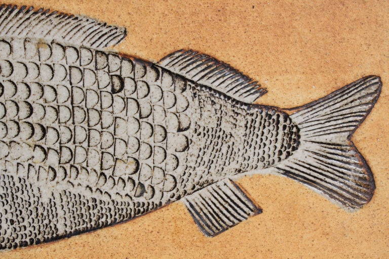 Roger Capron French (1922–2006) large ceramic tile evocative of a prehistoric fossil fish, executed in intricate, dimensional detail and finished in black off white. Signed