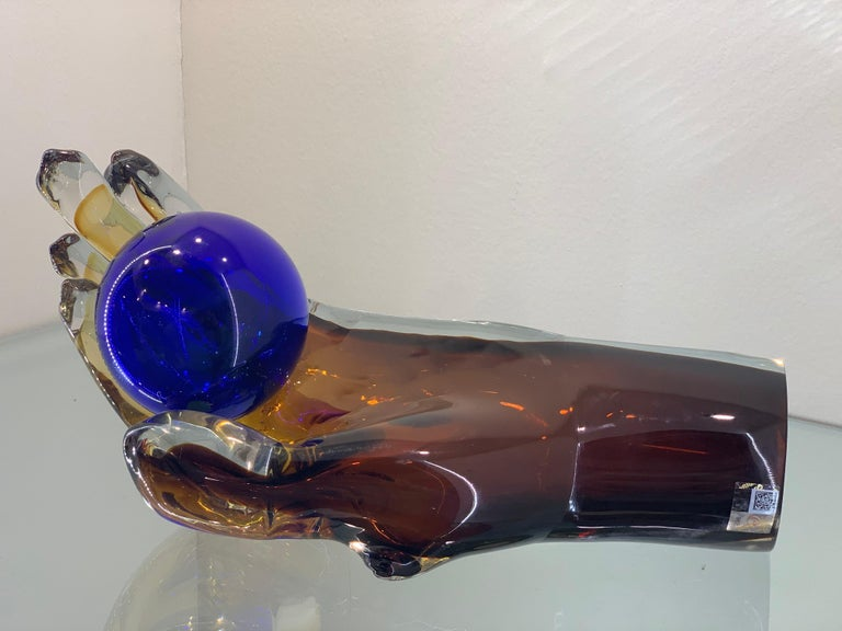 A modern Murano glass sculpture portraying an epic hand . Dark Amber with blue Sphere.