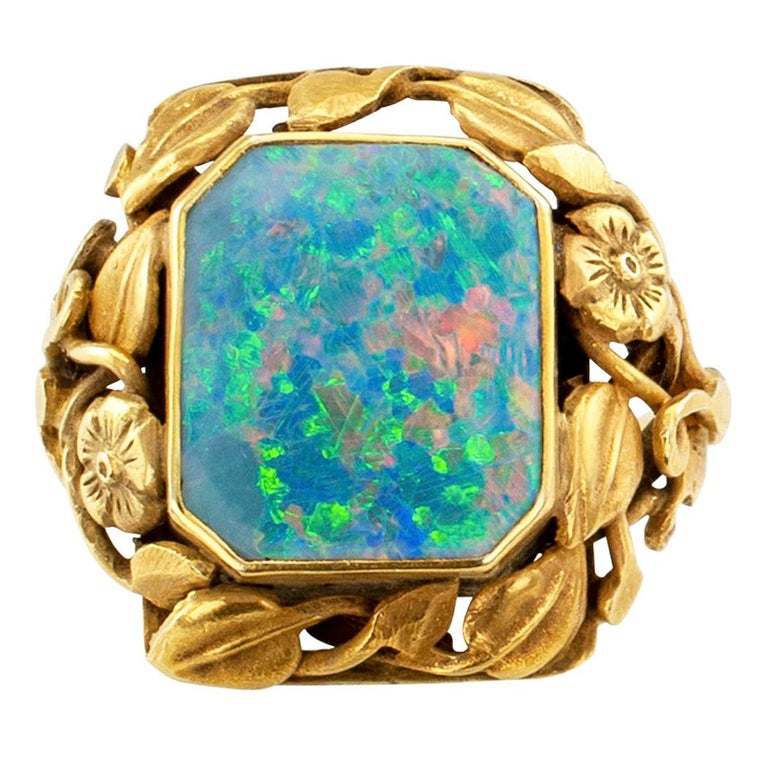 Arts and Crafts black opal and gold ring circa 1900.  Showcasing a bezel-set, octagonal natural black opal framed by a lavish, winding garland of flowers and leaves to the shoulders and shank, mounted in 14-karat yellow gold with a matt finish