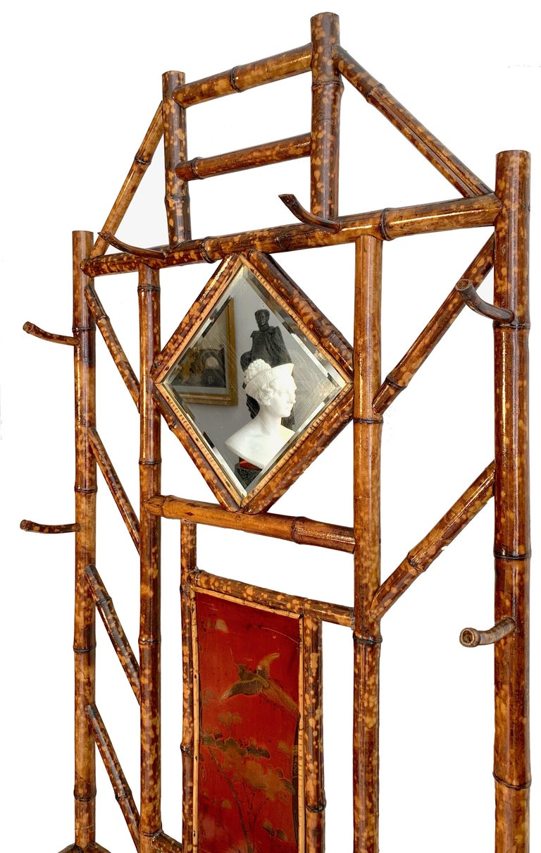 This elegant and rare bamboo wardrobe is decorated with painted lacquer panels in the Japanese taste and retains the original faceted mirror.