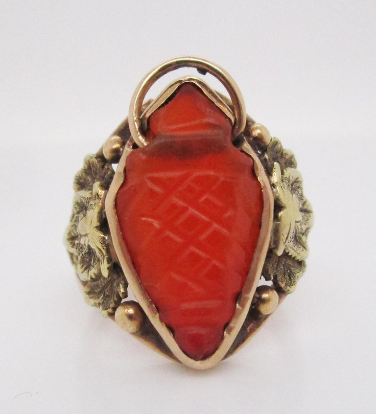 This gorgeous ring exemplifies the best of the Arts and Crafts movement in its spectacular combination of 14k yellow gold, repurposed carved carnelian, and hand-crafted grape and leaf motifs set ever so delicately on the shoulders! The center stone