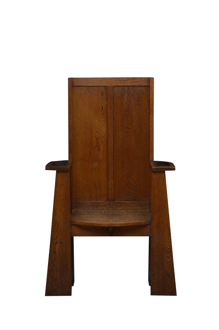 Stylish Arts & Crafts solid oak hall chair, having simple, double paneled back and shaped seat with a new cushion flanked by overhanging arms with umbrella holders, standing on tapering supports united by stretchers enclosing removable drip trays.