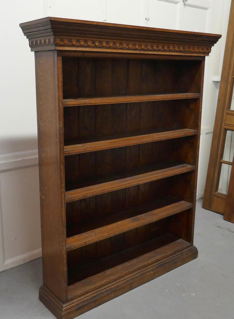 Arts and Crafts open oak bookcase with secret compartment  This oak bookcase has reeded fronts to the shelves and sides, it stands on a neat plinth with large carved cornice at the top The bookcase is in good attractive condition This one hides