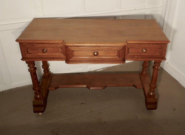 Arts & Crafts pitch pine writing table   A good heavy quality pitch pine side table or writing table in the Arts & Crafts style There are 3 drawers along the break side, they have turned pitch pine knobs The desk has a shaped edge to the top and