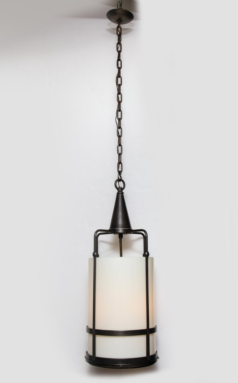 Arts & Crafts style heavy aged bronze frame lantern pendant with a thick white milk glass diffuser. Lantern houses 4-light sources which use Edison type bulbs. Rewired for use in the USA. Lantern body measures 37