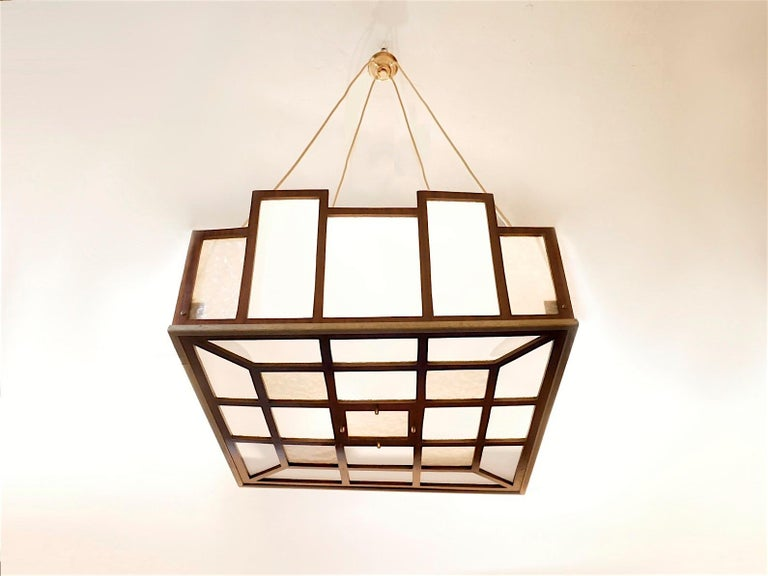Extra large sized early 20th century pendant lamp, Arts & Crafts design with a very light weight wooden geometrical structure in mahogany wood veneer matched with brass components, bi-colored acrylic diffuser.