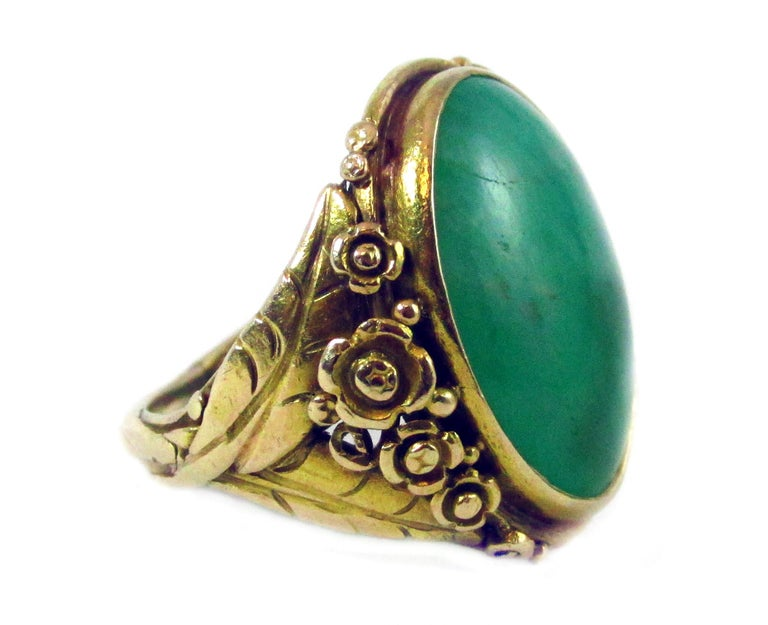 Arts and Crafts period 14 karat yellow gold oval cabochon Jadeite ring with intricate detailed gold work around the bezel and along the shank. A wonderful floral design embellishes the center gemstone giving this ring it's unique character. The ring